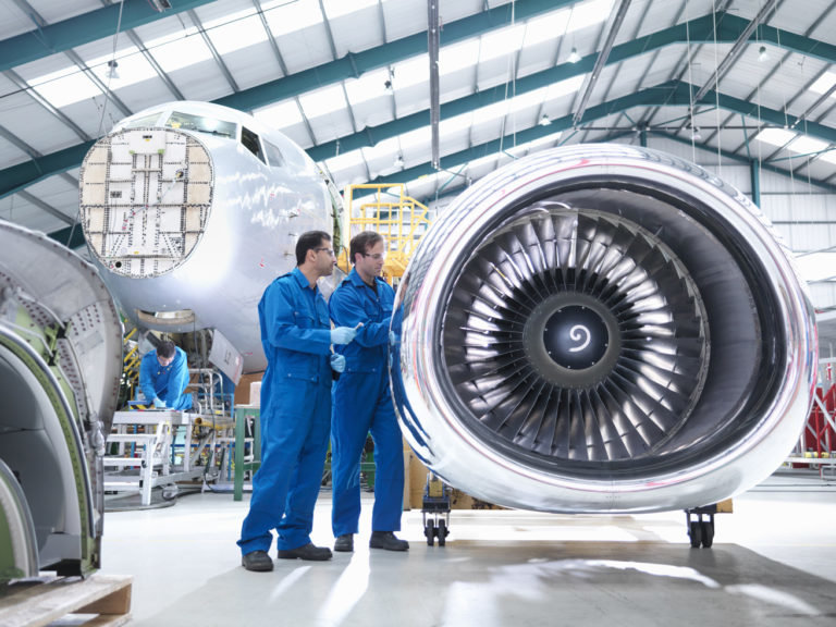 Engineers working on engine in aircraft maintenance factory